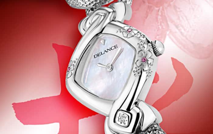 Kanon acier : Montre en acier sertie de 3 fleurs gravées avec un cœur de saphir rose, cadran nacre blanche, cabochon en acier avec un diamant à 6h, bracelet en gourmette