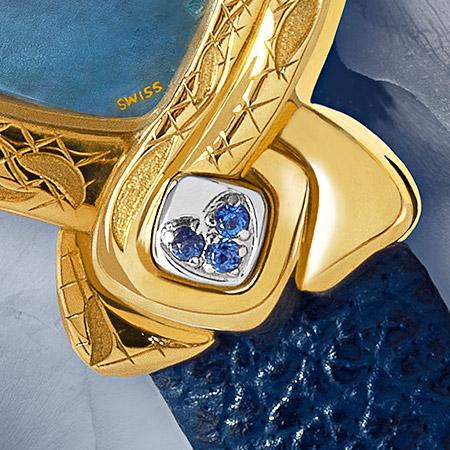 Fang Yin, Subtile montre en or délicatement gravée et son cadran de nacre bleu ornée d'un bluet. Le cabochon en acier est serti de 3 saphirs. Le bracelet de cuir bleu l'achève en beauté.